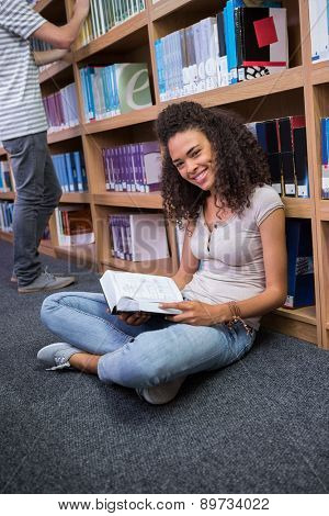Pretty student sitting on floor reading book in library at the university