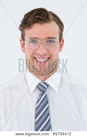 Geeky businessman smiling at camera on white background