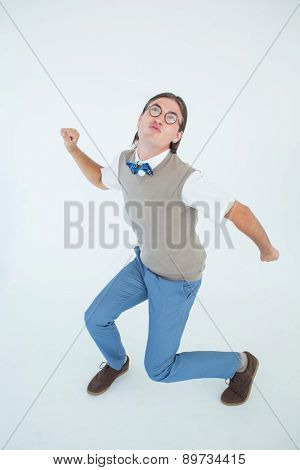 Geeky hipster dancing and smiling on white background