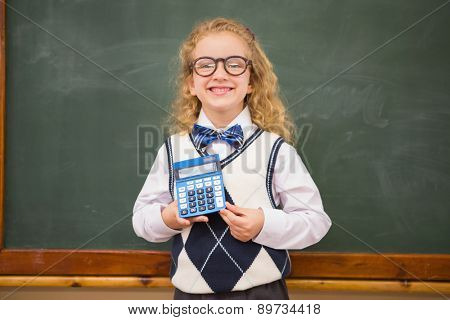Smiling pupil holding calculator at elementary school