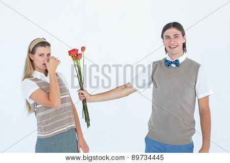 Geeky hipster offering red roses to his girlfriend on white background