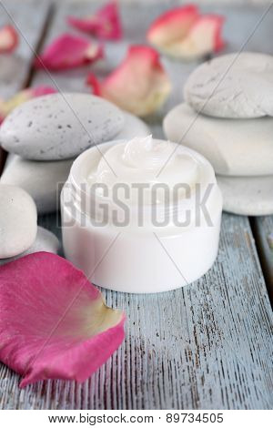Cosmetic cream with rose petals and spa stones on wooden background