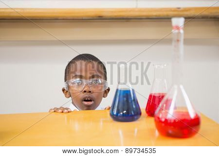 Shocked pupil looking at liquids at elementary school