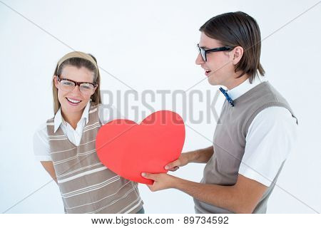 Geeky hipster offering red heart to his girlfriend on white background