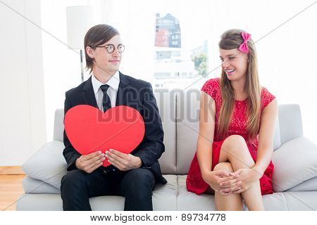 Cute geeky couple with red heart shape on the couch