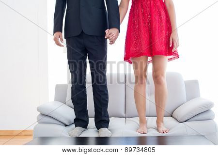 Geeky couple standing hand in hand on the couch at home