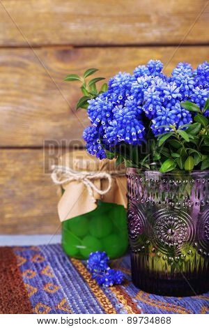 Blue bell flowers with maraschino cherry in glass jar on wooden background