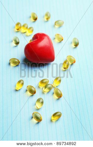 Red heart and cod liver oil, on blue background