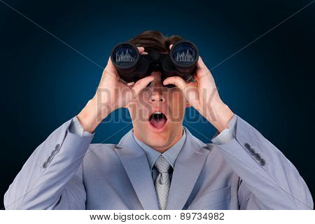 Suprised businessman looking through binoculars against blue background with vignette