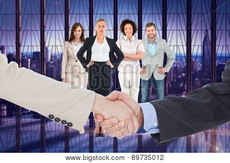 Smiling business people shaking hands while looking at the camera against room with large window looking on city