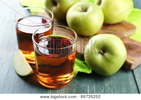 Glasses of healthy fresh juice of apples on wooden background