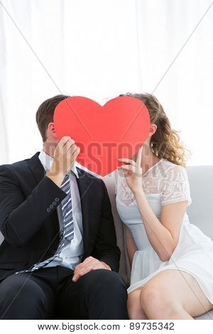 Couple kissing behind heart card on the couch