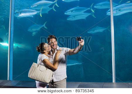 Happy couple taking a selfie at the aquarium