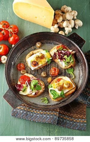 Tasty sandwiches on old pan, on wooden table