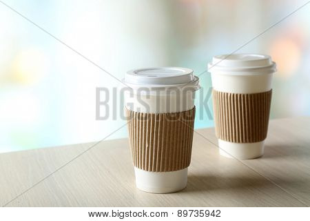 Paper cups of coffee on table on bright background