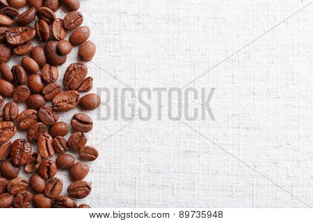 Frame of coffee beans on color sackcloth background