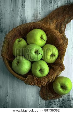 Green apples in bowl with fabric on wooden table, top view