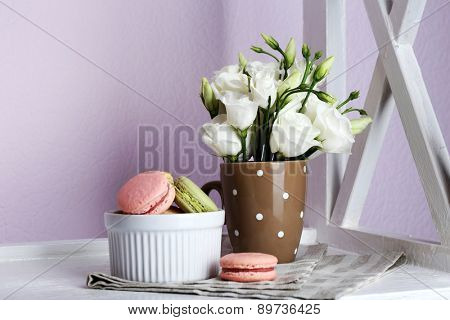 Delicious macaroon with beautiful flowers on light background
