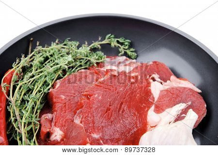 raw beef meat with thyme and pepper on black ceramic pan isolated on white background