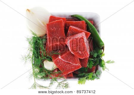 fresh uncooked beef meat slices over white bowls ready to prepare with green hot peppers and greenery isolated over white background