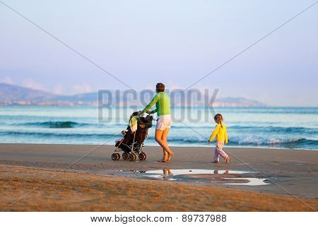 Mother Walking On Beach With Her Daughter And Baby