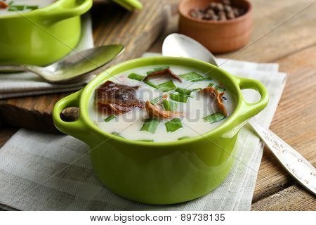 Mushroom soup on wooden table with napkin, closeup
