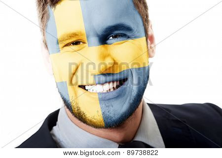 Happy man with Sweden flag painted on face.