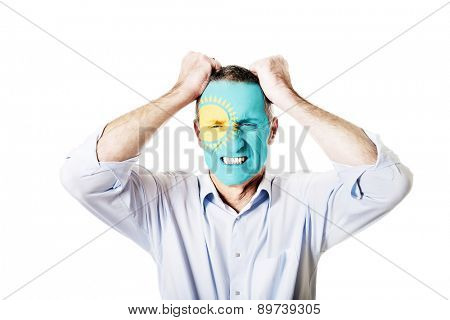 Mature man with Kazakhstan flag painted on face.