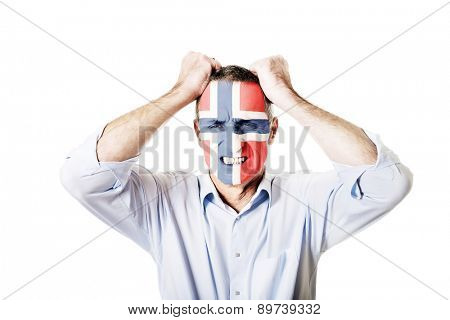 Mature man with Norway flag painted on face.