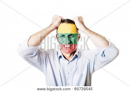 Mature man with Lithuania flag painted on face.