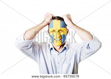 Mature man with Sweden flag painted on face.