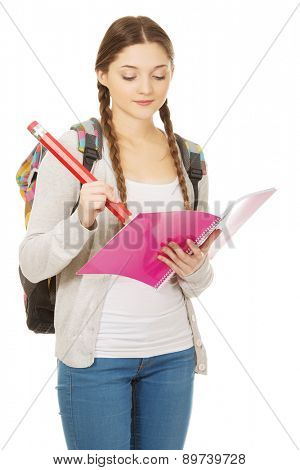 Casual teen woman writing with huge pencil.