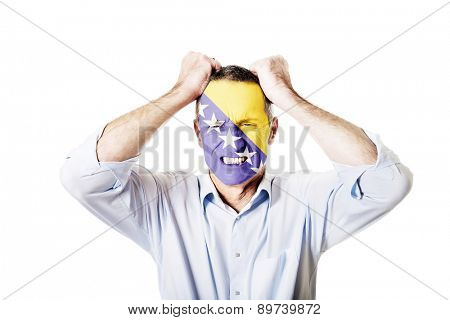 Angry mature man with Bosnia and Herzegovina flag on face.