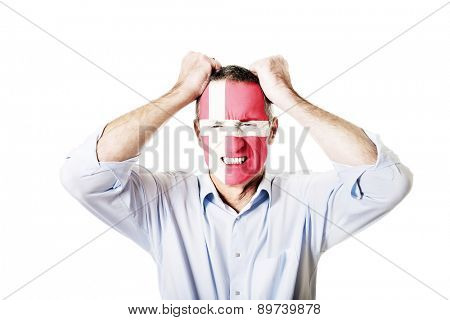 Mature man with Denmark flag painted on face.
