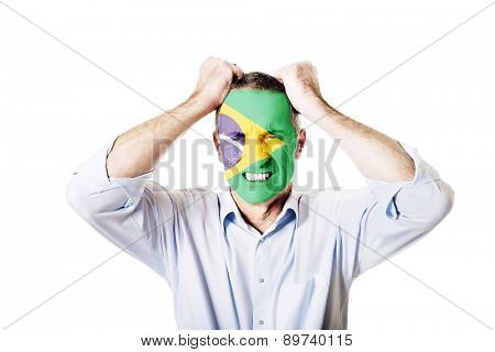 Angry mature man with Brasil flag painted on face.