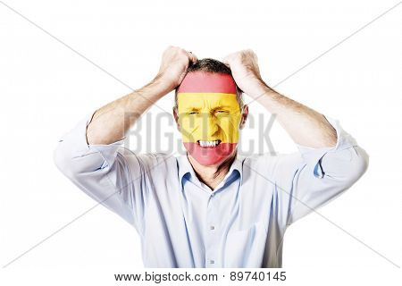 Mature man with Spain flag painted on face.