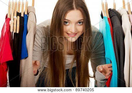 Happy teen woman between clothes on hanger.