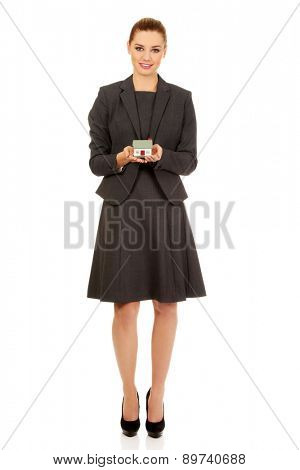 Happy businesswoman presenting house model.