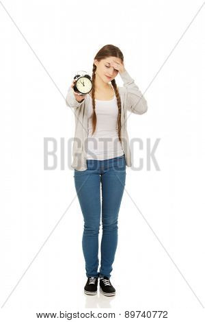 Exhausted teenage woman with alarmclock.