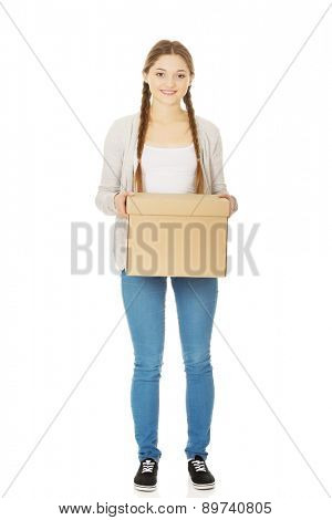Happy teenage woman holding carton box.