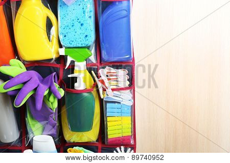 Household chemicals in holder hanging on wooden door, closeup