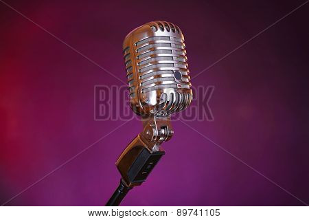 Retro microphone on colorful blurred background