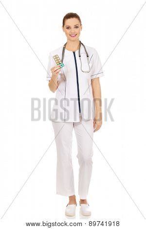 Happy doctor woman holding pills.