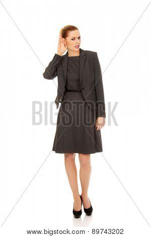 Beautiful business woman overhearing a conversation.