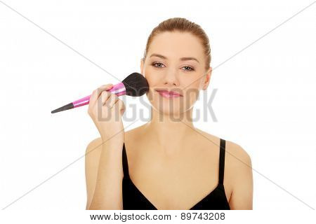 Beautiful spa woman with brush doing make up.