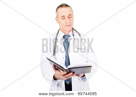 Mature male doctor holding notebook.