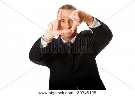 Smiling mature businessman gesturing frame.