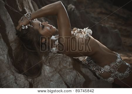 Beautiful woman in shells accessories lying on the beach