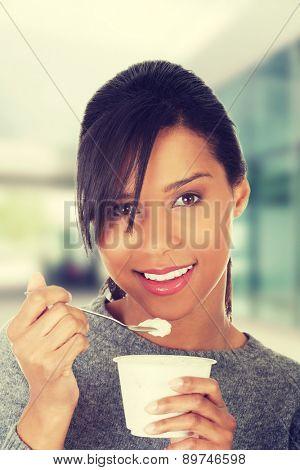 Happy healthy woman eating yoghurt