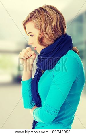 Young woman coughing because of flu